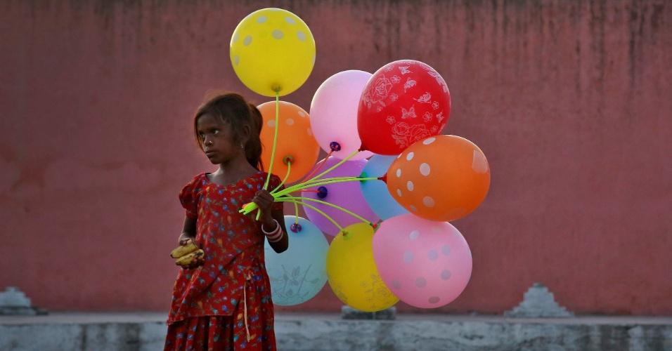 15.set.2016 - Jovem vende balões pelo rio Yamuna, no último dia do festival Ganesh Chaturthi em Nova Deli, na Índia