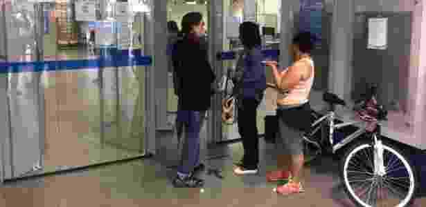 Pessoas buscam informações em agência fechada da Caixa na região central de SP - Ricardo Marchesan/UOL - Ricardo Marchesan/UOL