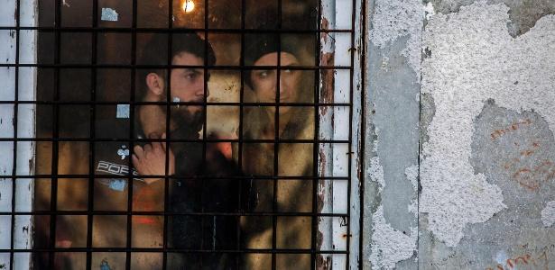 Imigrantes olham pela janela em campo de refugiados próximo a Belgrado, na Sérvia