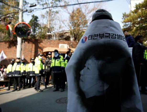 Apoiador de Park Geun-hye, envolvido em bandeira com a imagem dela, se posiciona na frente da casa da ex-presidente, onde também estão policiais e jornalistas