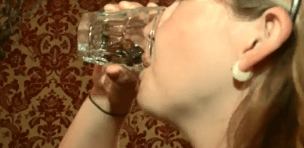 Jovem bebe drinque com o dedo no copo