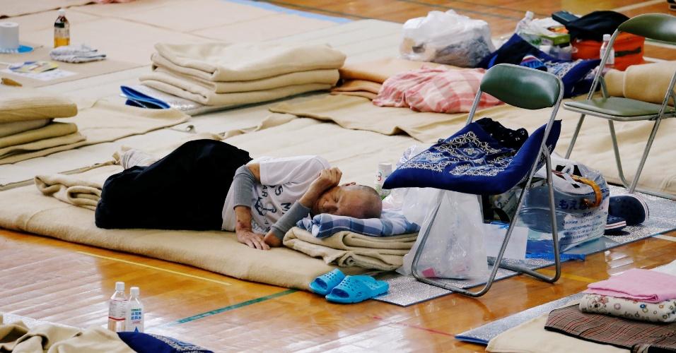 12.jul.2018 - Pessoa descansa em abrigo improvisado após ter residência invadida pelas águas em Kurashiki