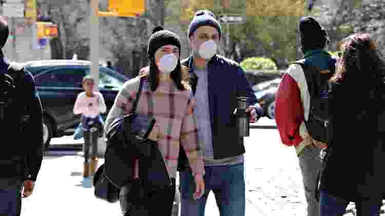 Casal com máscaras de proteção caminham pela 5ª avenida, em Nova York; assim como no Brasil, EUA passam pela fase da mitigação de casos - Cindy Ord/AFP - Cindy Ord/AFP