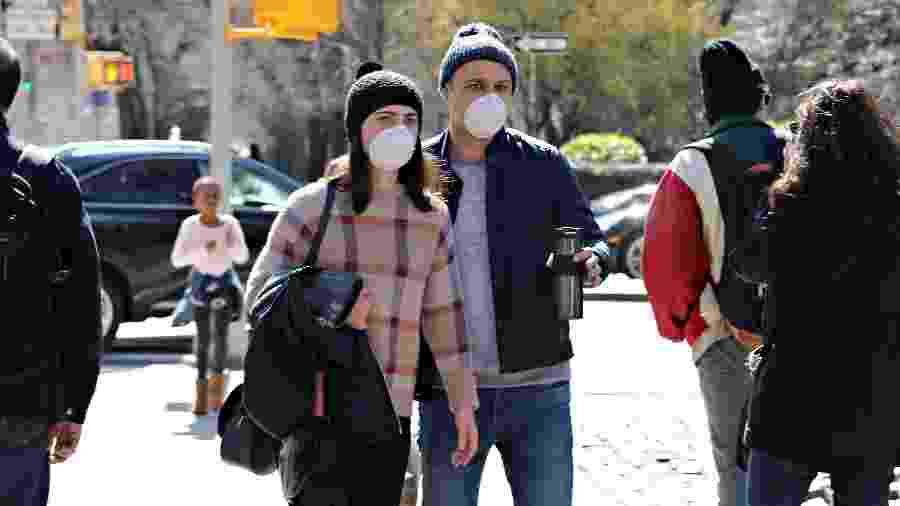 Coronavírus: Casal com máscaras de proteção caminham pela 5ª avenida, em Nova York (EUA) - Cindy Ord/AFP