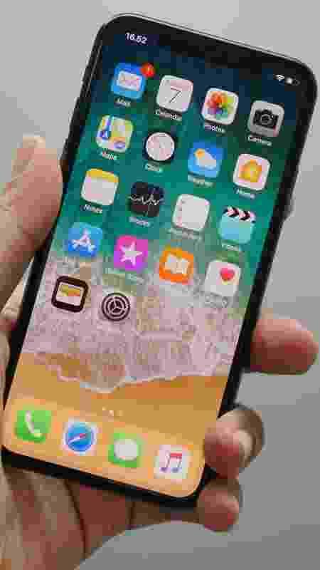 Mão segurando um iPhone X com tela inicial de aplicativos - Unsplash - Unsplash