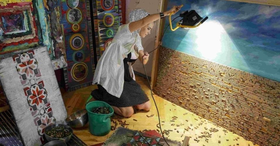 27.jul.2015 - A artista Dariya Marchenko produz em seu estúdio, localizado em Kiev, imagens feitas com cartuchos de balas trazidos da linha de frente do leste da Ucrânia. Marchenko considera sua arte filosófica, onde cada elemento tem um significado oculto. As obras feitas com cartuchos representam a vida do ser humano encerrada de forma brutal