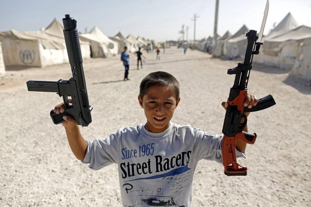 24.set.2015 - Menino sírio brinca com armas de brinquedo em um campo de refugiados em Sanliurfa, na Turquia. Turquia ofereceu cooperação à União Europeia (UE) para enfrentar a crise de refugiados com a contenção dos fluxos rumo à Europa em troca de facilidades para a obtenção de vistos