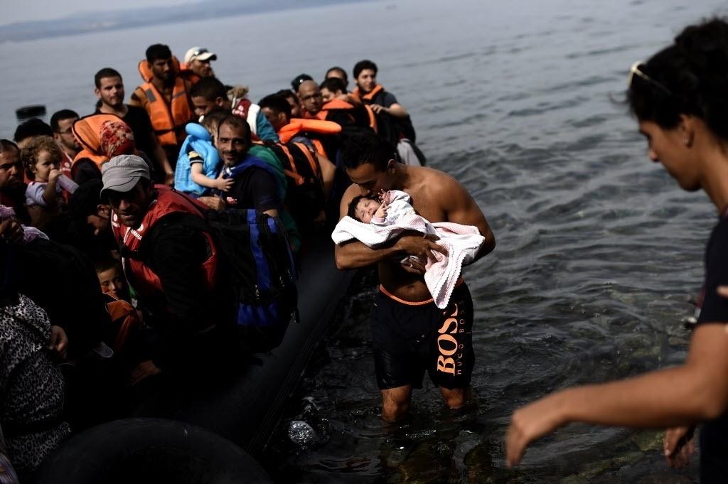 26.set.2015 - Refugiado beija seu bebê ao conseguir chegar em um bote inflável à ilha grega de Lesbos depois de atravessar o mar Egeu da Turquia. O alto comissário da Nações Unidas para os refugiados, António Guterres, saudou a decisão da União Europeia de disponibilizar 1 bilhão de euros para agências internacionais que administram campos de refugiados em países vizinhos da Síria, mas afirmou que é preciso fazer mais para recolocar os migrantes
