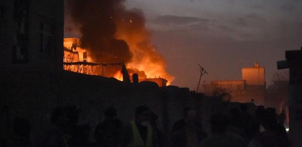 Transeuntes observam chamas do restaurante francês Le Jardin, atingido por um carro-bomba, em Cabul
