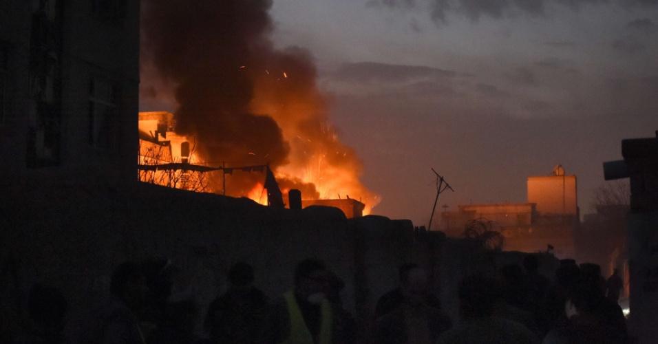1º.jan.2016 - Transeuntes observam as chamas do restaurante francês Le Jardin, atingido por um carro-bomba, em Cabul, no Afeganistão