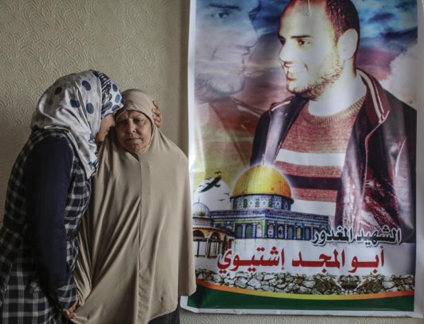 Mãe (à direita) e irmã de Mahmoud Ishtiwi (no pôster), que foi morto por seus companheiros militares no Hamas, acusado de roubo e sexo gay em Gaza