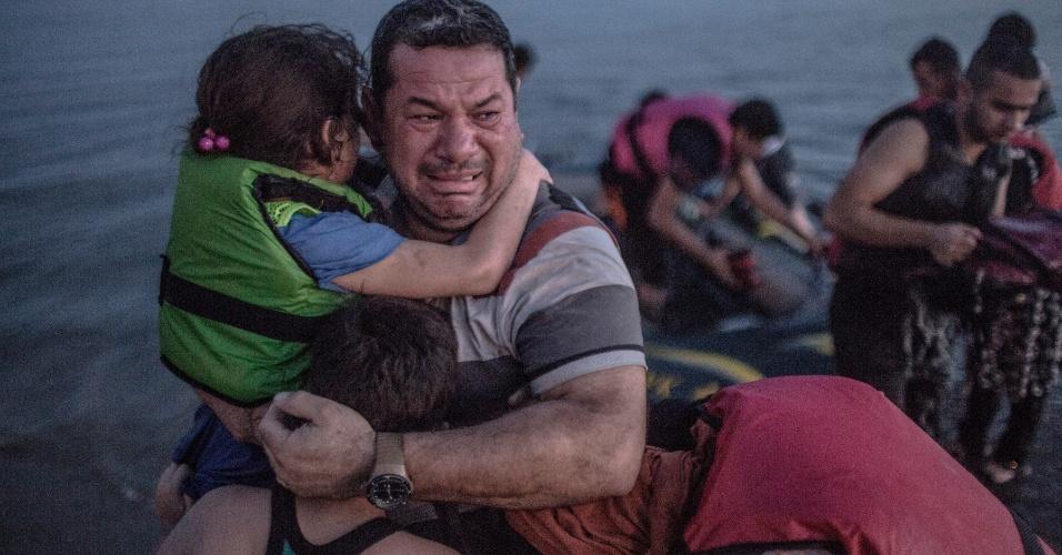 """19.abr.2016 - Laith Majid, um refugiado iraquiano chora de lágrimas de alegria, segurando os filhos, depois que eles chegaram em segurança em Kos, Grécia, em 15 de agosto de 2015. Mauricio Lima, Sergey Ponomarev, Tyler Hicks e Daniel Etter do jornal """"The New York Times"""" ganharam o Prêmio Pulitzer com uma série de fotos sobre refugiados na Europa"""