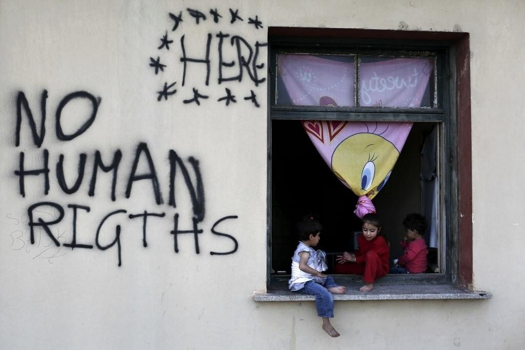 19.mai.2016 - Crianças sentam na janela de um acampamento de refugiados e imigrantes improvisado no vilarejo de Idomeni, na Grécia, próximo à fronteira com a Macedônia. Ao lado delas se lê as palavras