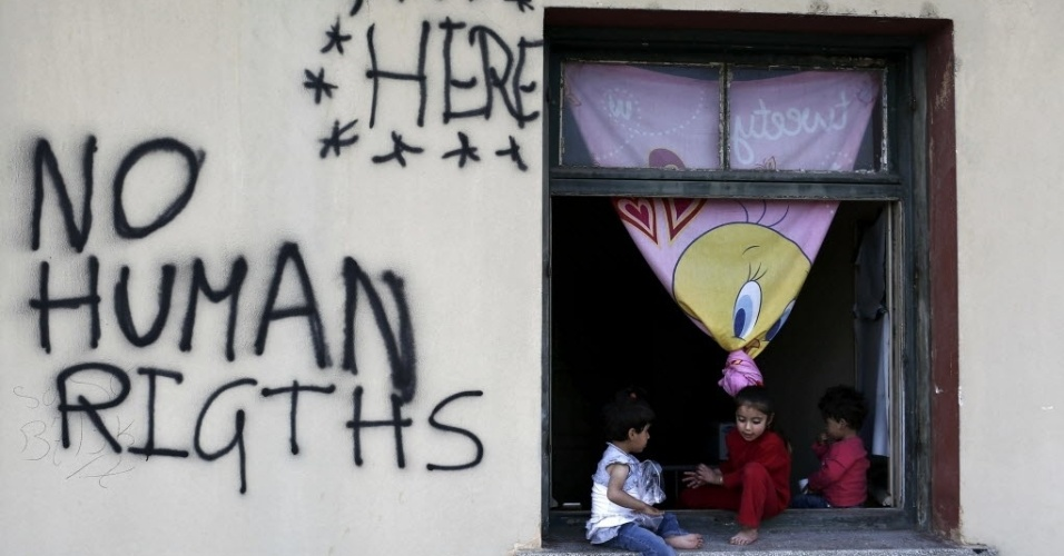 """19.mai.2016 - Crianças sentam na janela de um acampamento de refugiados e imigrantes improvisado no vilarejo de Idomeni, na Grécia, próximo à fronteira com a Macedônia. Ao lado delas se lê as palavras """"Aqui nenhum direitos humanos"""""""