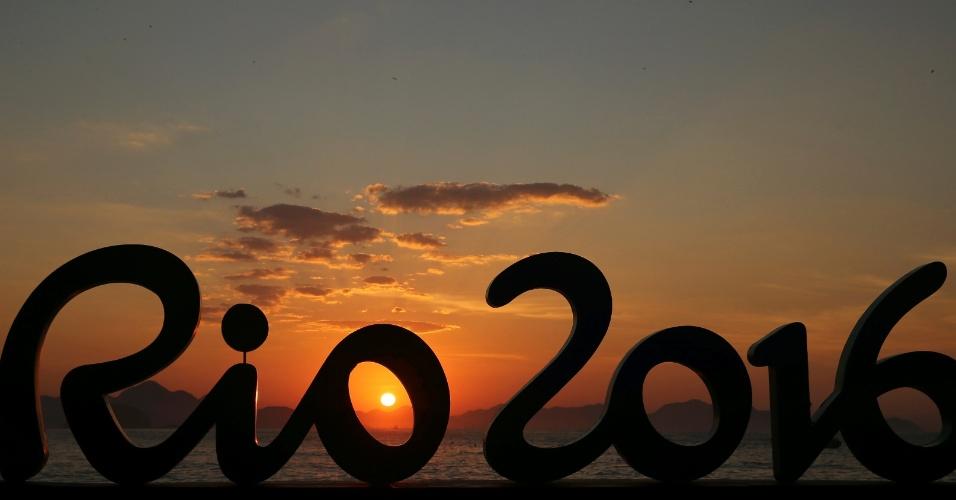 Sol nasce atrás do símbolo das Olimpíadas Rio 2016, na orla da praia de Copacabana, zona sul do Rio de Janeiro