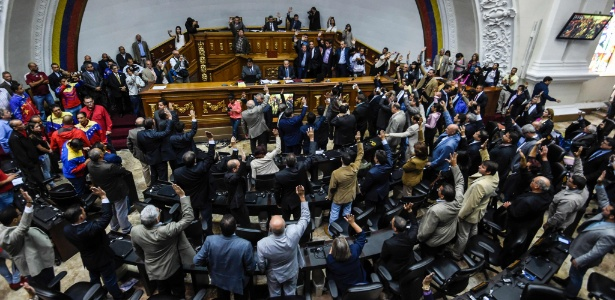 Deputados da oposição levantam a mão ao votar a favor da abertura de processo político contra o presidente Nicolás Maduro, durante sessão na Assembleia Nacional, em Caracas, na Venezuela