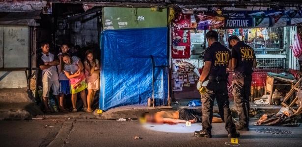 Policiais observam homem assassinado nas Filipinas