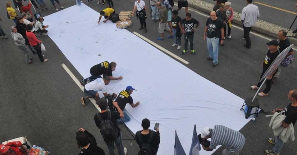 21.mai.2017 - No Rio de Janeiro, manifestantes se reuniram em frente ao hotel Copacabana Palace para cobrar prisão aos corruptos e eleições diretas. Um pano branco foi estendido no chão, para os manifestantes escreverem mensagens sobre a crise política