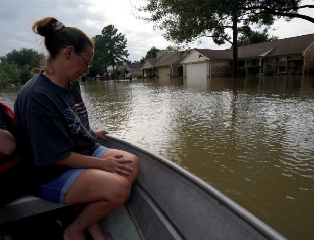 Mulher é transportada através das águas que inundam as ruas de seu bairro em Houston - Rick Wiking/Reuters