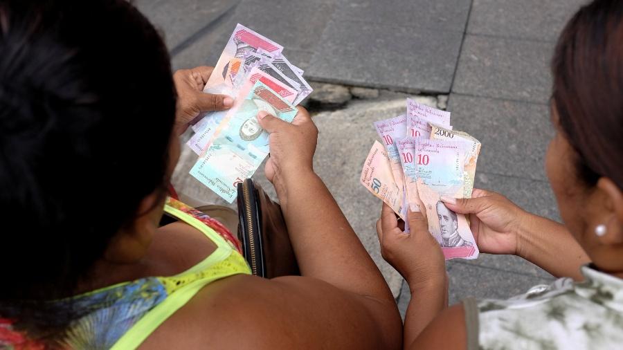 Venezuelanas contam notas de bolívar soberano, a nova moeda do país - Marco Bello/Reuters