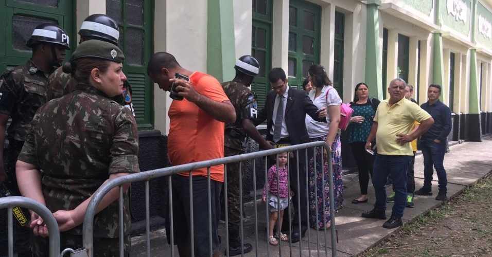 28.out.2018 - Pai com filha pequena passa por revista com detector de metais, no local de votação do presidenciável Jair Bolsonaro, na Vila Militar, no Rio de Janeiro