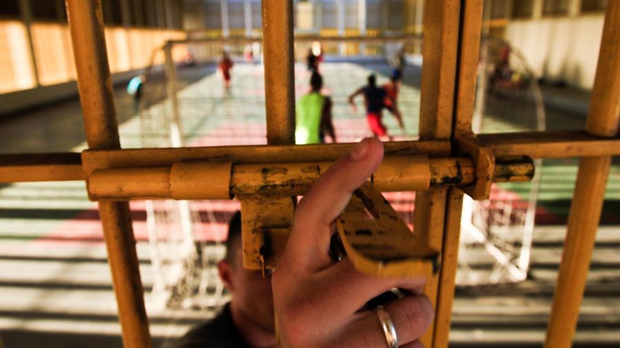 Agente fecha portão enquanto menores jogam futebol na quadra da Fundação Casa, na unidade de Osasco - 12.jul.2010 - Marcelo Justo/Folhapress