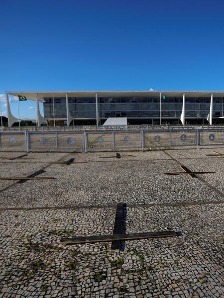 Ativistas montam cruzes em memória das pessoas que morreram pela covid e contra o presidente brasileiro Jair Bolsonaro, em frente ao Palácio do Planalto, em Brasília - ADRIANO MACHADO/REUTERS
