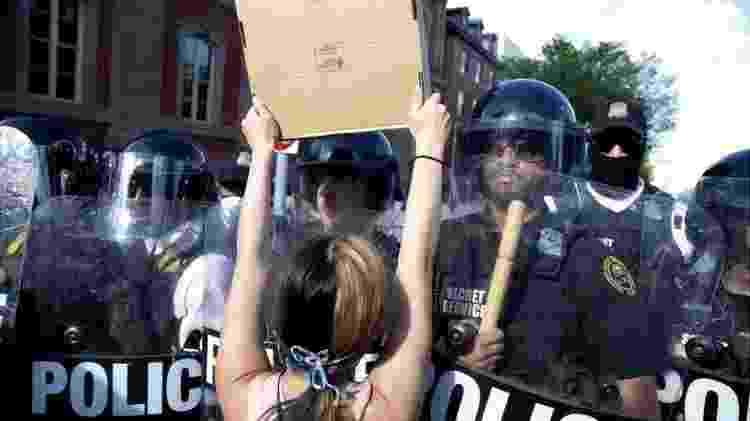 Mulher protesta enquanto policiais bloqueiam a praça Lafayette, no centro de Washington - Getty Images - Getty Images