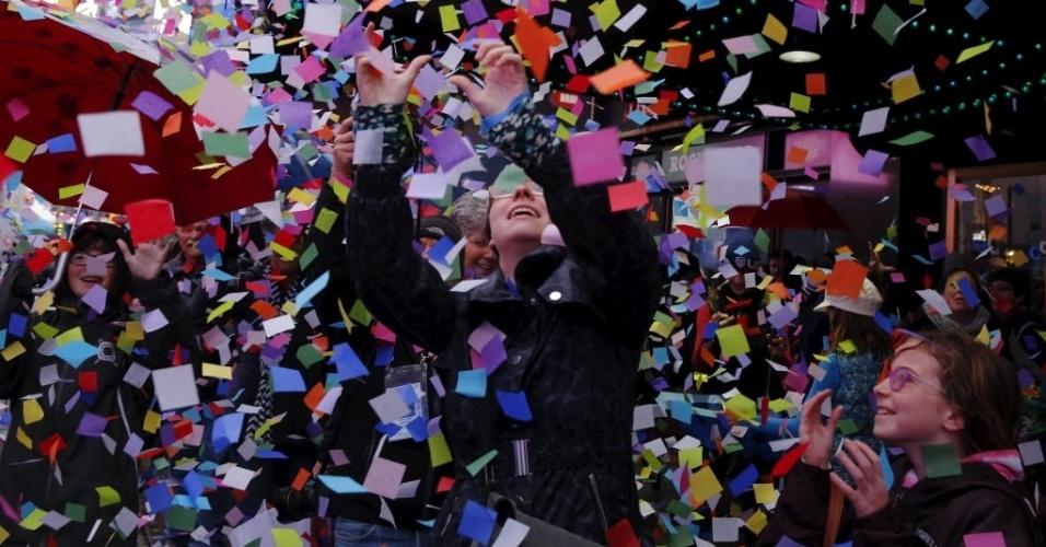 29.dez.2015 - Pedestres param e observam chuva de confetes na Times Square, em Nova York (Estados Unidos). Famoso ponto turístico norte-americano recebeu nesta terça um teste da chuva de confetes que ocorre tradicionalmente na virada do ano