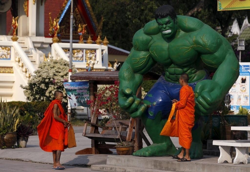 3.mar.2016 - Monges budistas passam por uma estátua do personagem Hulk no templo Tamru, em Samut Prakan, na Tailândia. A obra do herói foi colocada no templo budista para atrair mais visitantes