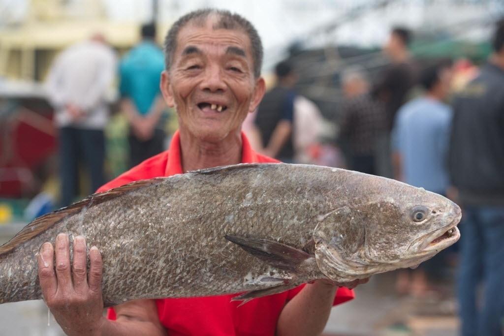 6.mar.2016 - Pescador exibe peixe que acabou de pegar em uma doca na cidade de Qionghai, na China