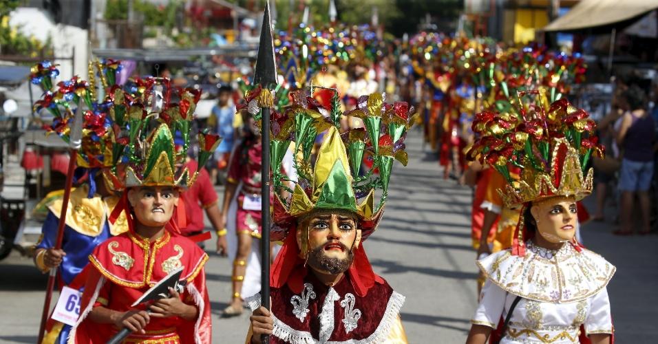 21.mar.2016 - Penitentes mascarados participam de parada religiosa em celebração à Semana Santa em Mogpog, na região central das Filipinas