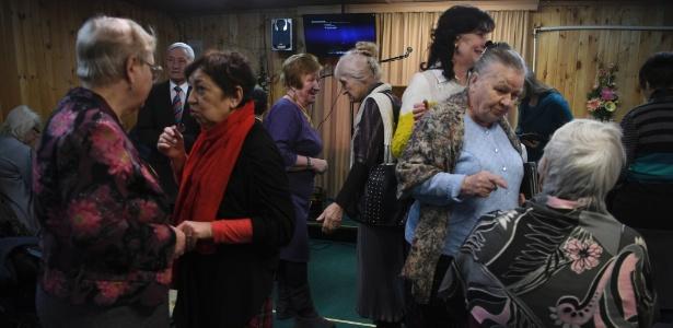 Membros das Testemunhas de Jeová conversam durante culto em Vorokhobino