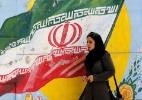 Irã: aumenta a escalada de tensões com EUA e seus aliados - Mulher passa em frente a pintura com bandeira do Irã em Teerã