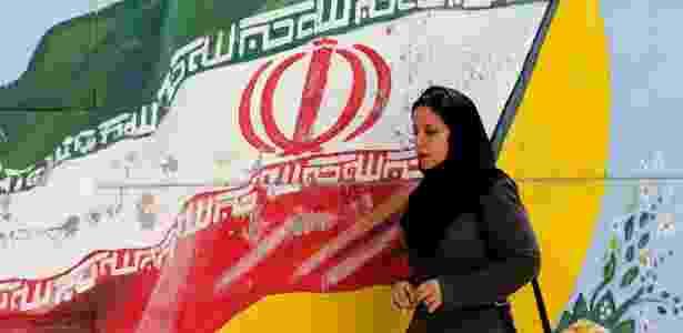 Mulher passa em frente a pintura com bandeira do Irã em Teerã