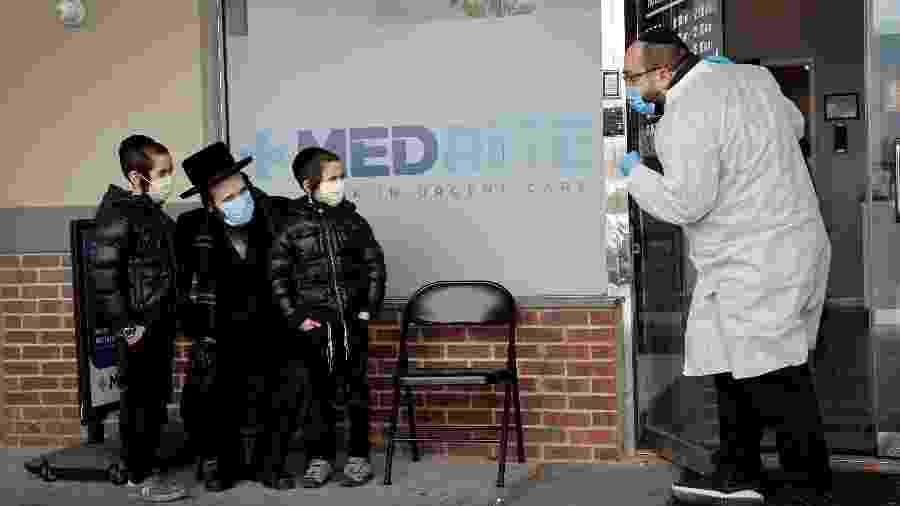 Um judeu ortodoxo e duas crianças usam máscaras protetoras enquanto conversam com um profissional de saúde do lado de fora de uma unidade de atendimento de urgência da MedRite, oferecendo testes para anticorpos contra a doença de coronavírus (COVID-19) no subúrbio de Spring Valley, Nova York - MIKE SEGAR/REUTERS