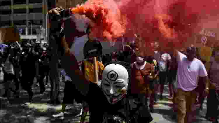 Homem segura granada de fumaça enquanto milhares de pessoas marcham em Denver, Colorado, onde um toque de recolher foi imposto no sábado à noite - Getty Images - Getty Images