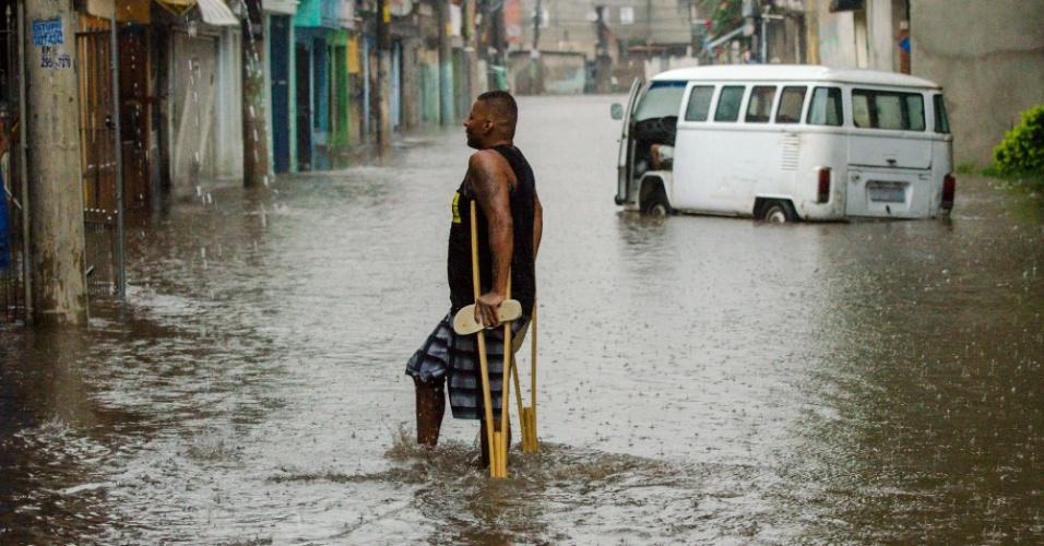 9.jan.2016 - Morador se arrisca ao passar por rua alagada no bairro da Vila União, distrito de Ponte Rasa, na zona leste de São Paulo, após o temporal que atingiu a cidade