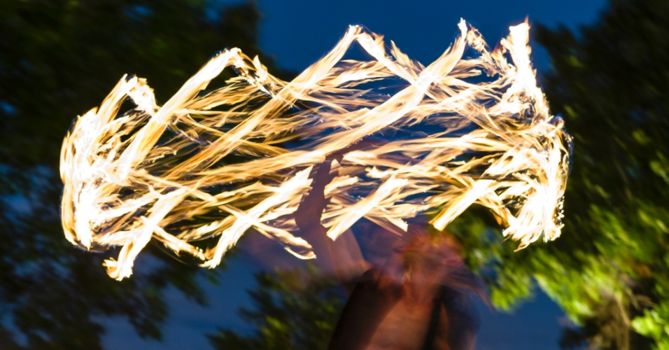 10.mar.2016 - Na Austrália, um artista performático deslumbra a plateia em um mercado de rua com uma coroa de fogo feita com um bastão flamejante