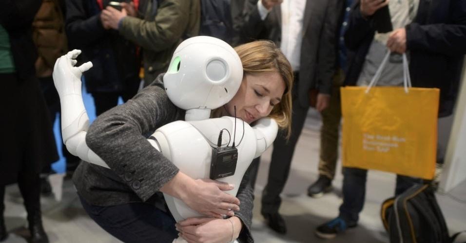 14.mar.2016 - Mulher abraça robô chamado Pepper na maior feira de computadores e software do mundo, em Hanover, na Alemanha