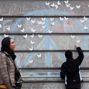 """Garoto escreve com giz """"Pare ISIS"""" (sigla em inglês para o grupo Estado Islâmico) em muro de praça no centro de Bruxelas"""