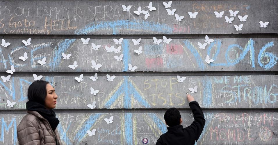 """24.mar.2016 - Garoto escreve com giz """"Pare ISIS"""" (sigla em inglês para o grupo Estado Islâmico) em muro de praça no centro de Bruxelas. Além das mensagens, o muro foi enfeitado com borboletas brancas de papel em homenagem às vítimas do terrorismo. Nesta semana, a capital belga e sede da União Européia foi alvo de dois ataques terroristas coordenados que deixaram mais de 30 mortos e cerca de 300 feridos"""