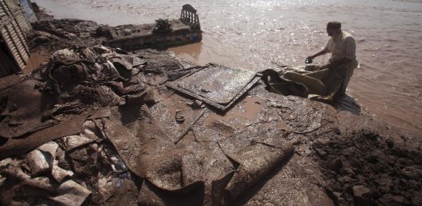 Homem tenta salvar o que restou de seus pertences após enchente na região de Sarband, nos arredores de Peshawar, no Paquistão