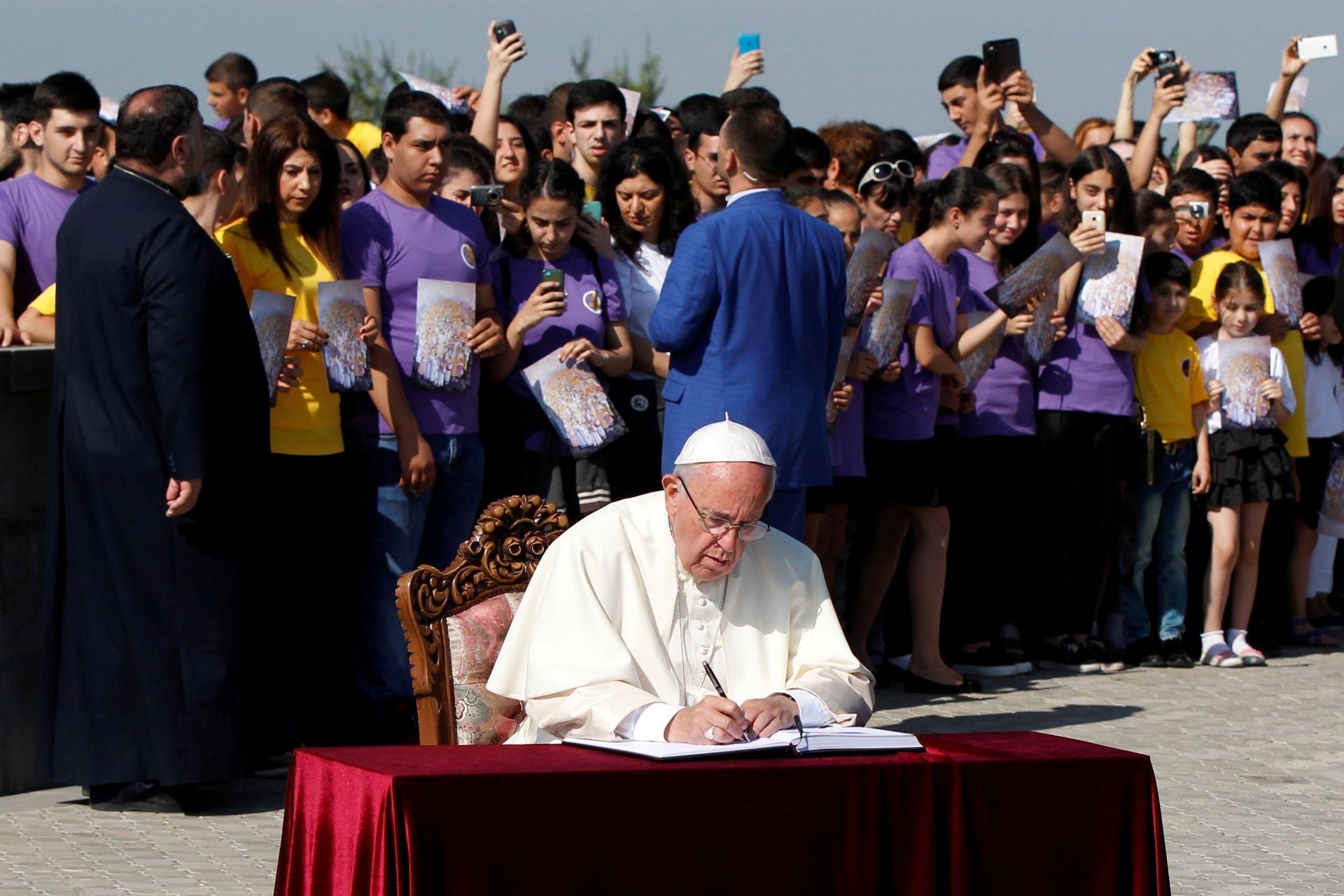 25.jun.2016 - Papa Francisco assina livro de visitas de memorial que lembra as vítimas do genocídio na Armênia, no início do século XX, em seu segundo dia de viagem ao país asiático. O pontífice fez uma oração e colocou uma coroa de flores no local