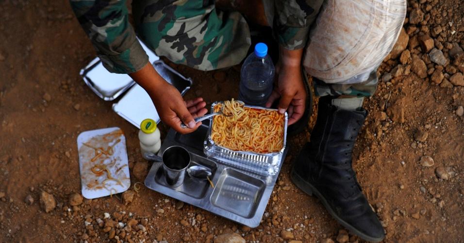 4.jul.2016 - Um dos soldados come massa com molho para quebrar o jejum do Ramadã, durante o pôr do sol