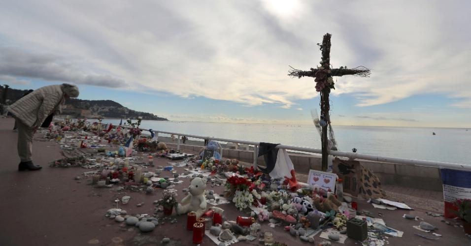 16.out.2016 - Francesa observa flores e velas, flores e brinquedos deixados em homenagem às vítimas do atentado em Nice, na França. Um caminhão atropelou e matou 86 pessoas que comemorava o Dia da Bastilha na orla da cidade em 14 de julho