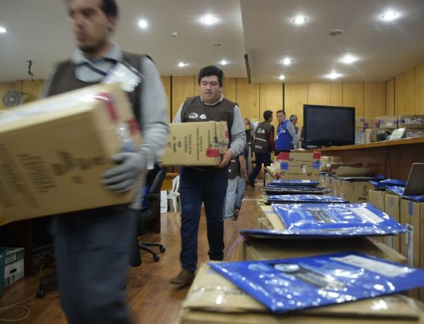 Membros do Conselho Eleitoral Nacional carregam caixas durante a contagem dos votos em Quito, no Equador
