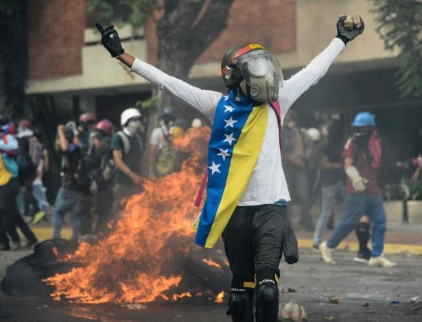 Manifestante de oposição protesta com pedras das mãos contra a autoridade de Maduro