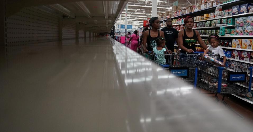 7.set.2017 - Pessoas caminham entre prateleiras vazias em supermercado de Miami Beach, na Flórida (EUA).