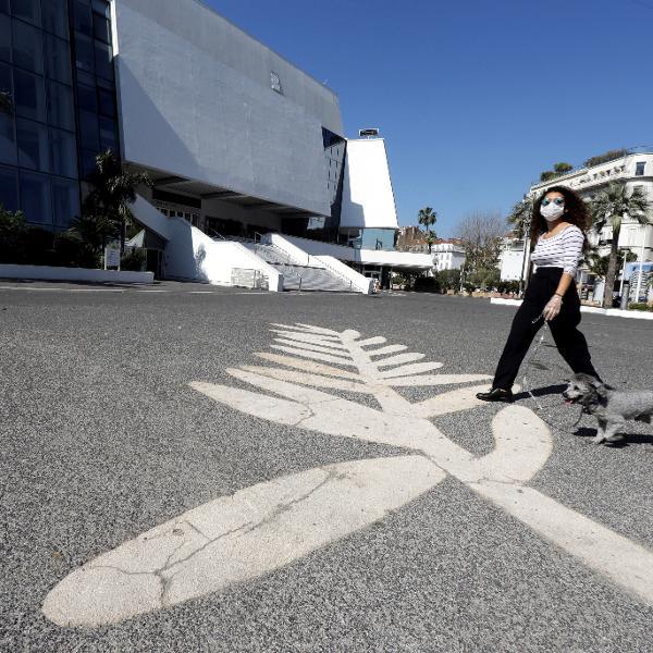 Mulher usando máscara de proteção passeia com cachorro sobre símbolo da Palma de Ouro em frente ao Palácio do Festival em Cannes